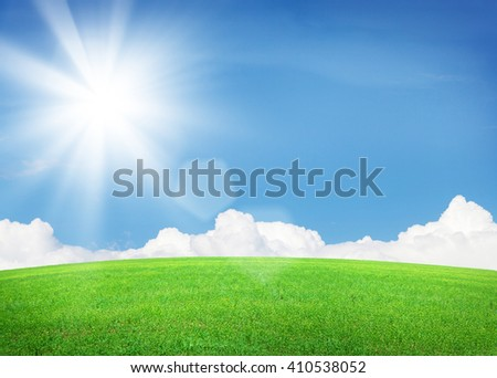 Green grass field and blue sky with clouds and bright sun. Summer landscape with endless grass field and bright sunny sky - stock photo