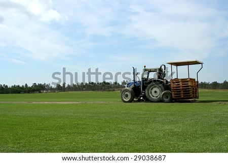 green grass field in alentejo with agricultural tractor