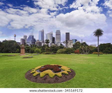green grass fields of Royal National Garden in downtown of Sydney, Australia, on a sunny summer day with skyscrapers in background - stock photo