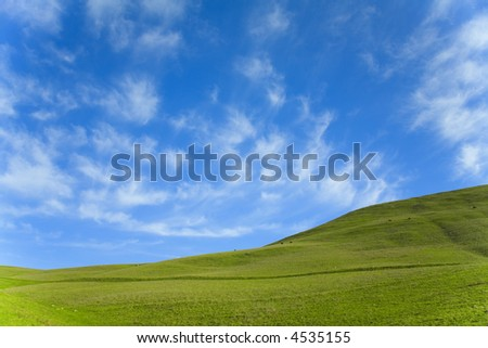 Green grass hillside and blue sky with clouds (4436)