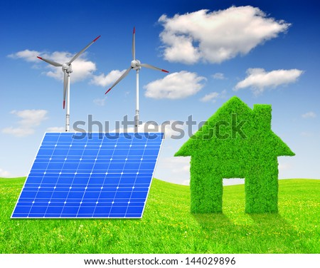 Green grass house symbol with solar panel and wind turbines on meadow - stock photo
