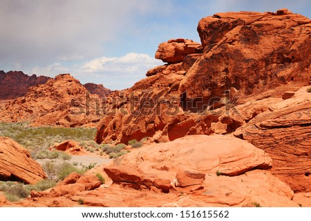 Green grass in foreground and red rocks at Valley of fire, Nevada - stock photo