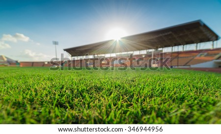 Green grass in soccer stadium. soccer field and blur stadium on blue sky. grass on selective focus   - stock photo