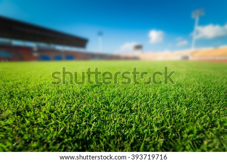 Green grass in soccer stadium. soccer field and blur stadium.  soccer stadium on blue sky.  - stock photo