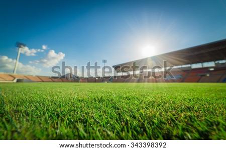 Green grass in soccer stadium. soccer field grass and blur stadium on blue sky. focus to grass.   - stock photo