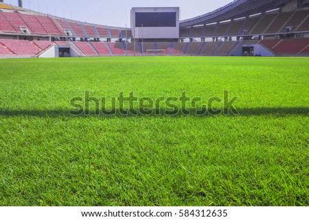 green grass in soccer stadium field with stadium on blue sky background green b27 green