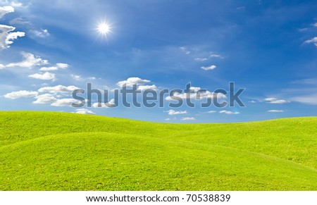 green grass meadow and bright sun in blue sky - stock photo