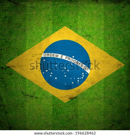 Green  grass of a Football playground with Brazil flag. Grunge background. - stock photo