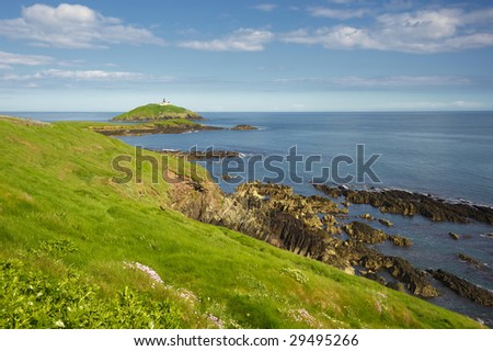 green grass on cliffs overlooking blue waters Ballycotton Bay, Co.Cork, Ireland with Ballycotton Lighthouse in distance