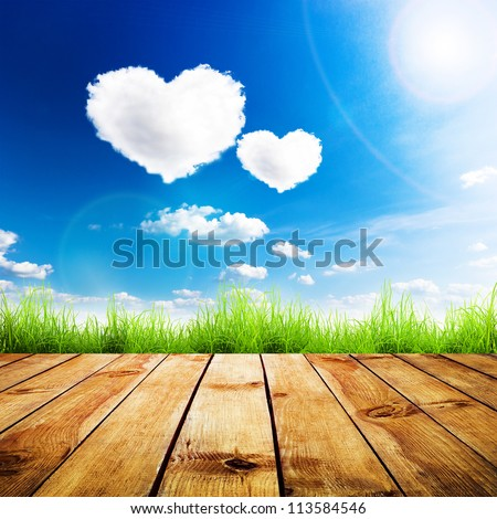 Green grass on wooden plank over a blue sky with hearts shape clouds. Beauty natural background - stock photo