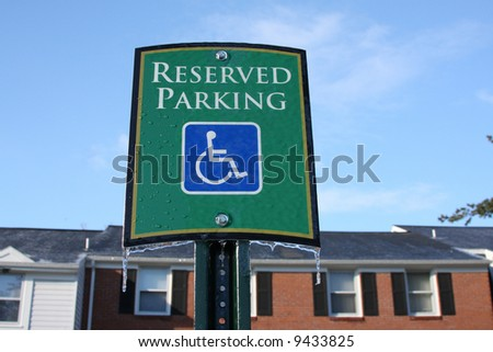 Green handicapped parking sign with icicles. Townhouses in background. - stock photo