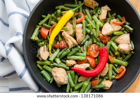 green haricot with peppers, meat and tomatoes on a frying pan