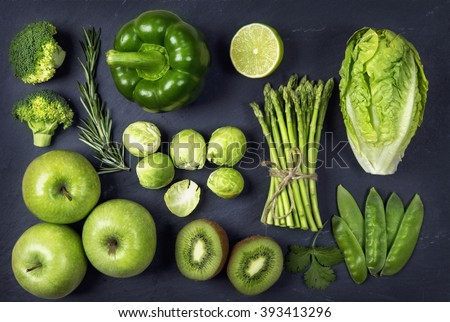 Green healphy vegetables and fruits on a black slates - stock photo