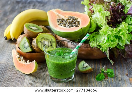 Green healthy kiwi tropical fruits smoothie with papaya and bananas - stock photo