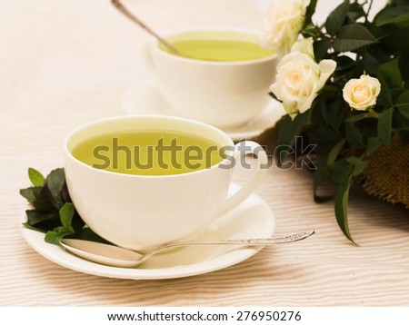 Green herbal  tea with mint in white cup with spoon