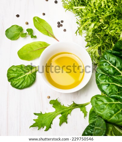 Green herbs salad with oil in white bowl - stock photo