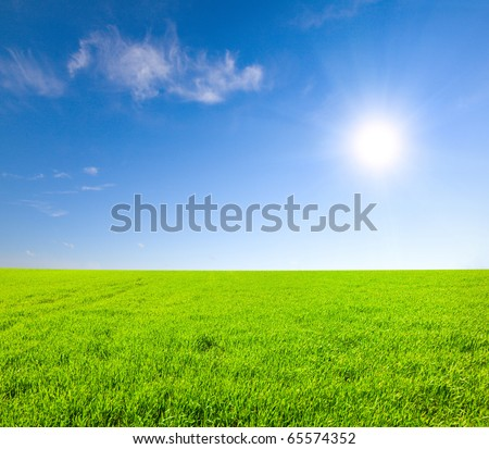 Green hill under blue cloudy sky whit sun - stock photo
