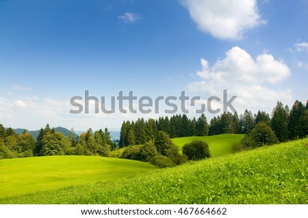 Green hills and forest under blue summer sky at alpine upland in South Germany; Hiking and recreation area
