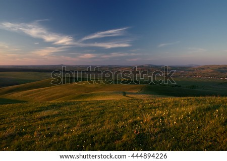 Green hills in the foothills with a country road on the background of the village at sunset under the blue sky with white clouds. Altai Mountains, Siberia, Russia. - stock photo