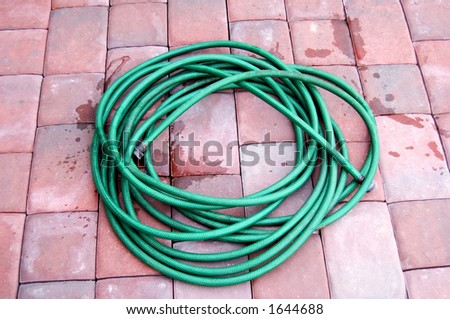 Green hose laying rolled on brick patio - stock photo