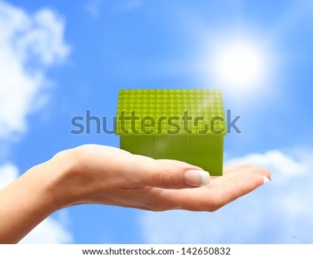 Green house in women hand against blue sky - stock photo
