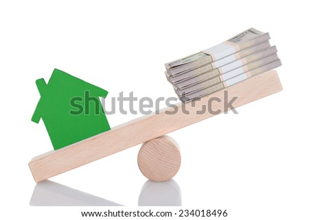 Green house model and dollar bundles balancing on seesaw isolated over white background - stock photo