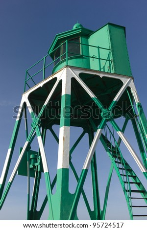 Green iron lighthouse on the coast of a sea in the Netherlands - stock photo