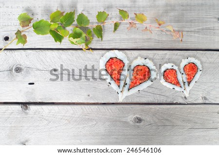 Green ivy vine and two hearts shape forming from four pieces of sushi on a vintage wooden table - stock photo