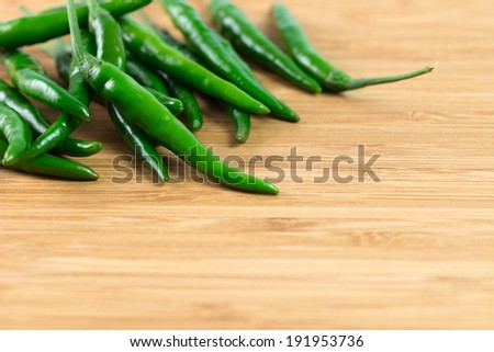 Green jalapeno pepper isolated on wooden chopboard - stock photo