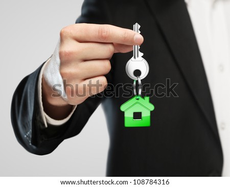 green key chain with key in hand  businessman - stock photo