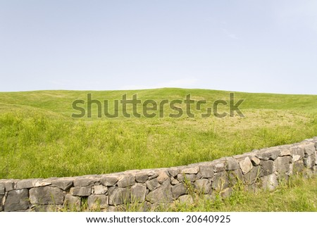 green landscape with a blue sky and a stone wall - stock photo