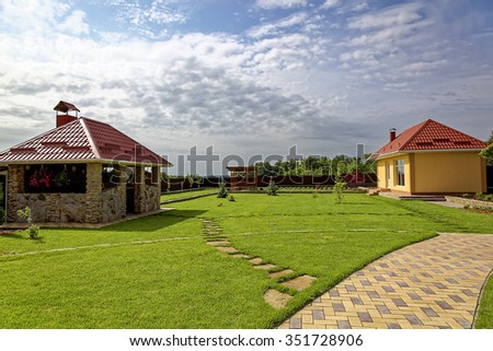 Green lawn and buildings in the backyard of the house.