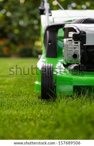 Green lawn mower on the green lawn  - stock photo
