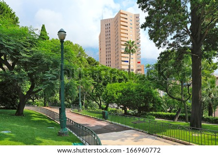 Green lawns and trees of small urban park and modern residential building on background in Monte Carlo, Monaco. - stock photo