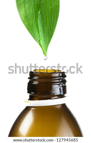 Green leaf and drop over a tube of cosmetics. White isolated