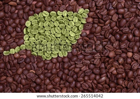 Green leaf made of coffee beans on the coffee beans background - stock photo