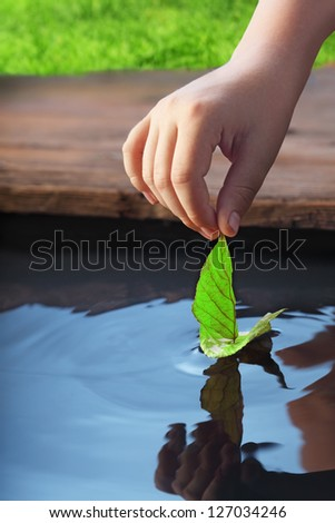 green leaf-ship in children hand - stock photo
