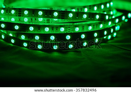 Green led strip on the background of textile - stock photo