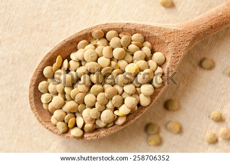 Green lentils portion on wooden spoon, healthy green raw seeds heap in studio shot, horizontal orientation, nobody.  - stock photo