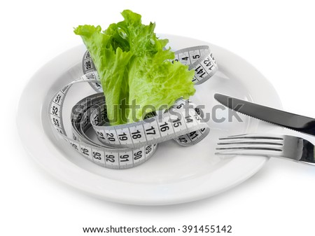 Green lettuce leaf with measuring tape on plate isolated on white - stock photo