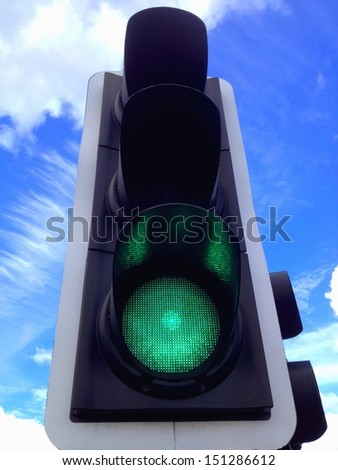 Green light on street signal with brilliant blue skies and clouds in background. - stock photo