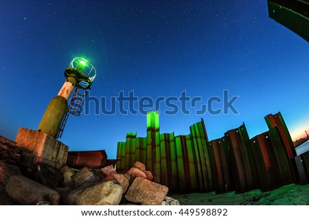 Green lighthouse on the remains of an old pier and the starry nightsky on the background - stock photo
