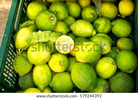 Green lime fruits in plastic box for sale.