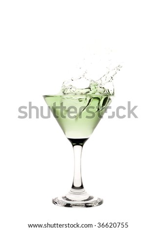 Green liquid splashing in a martini glass.