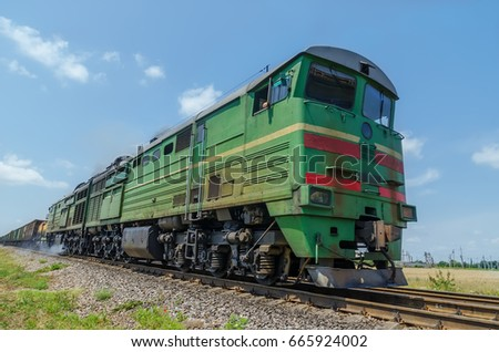 green locomotive in motion on the railway