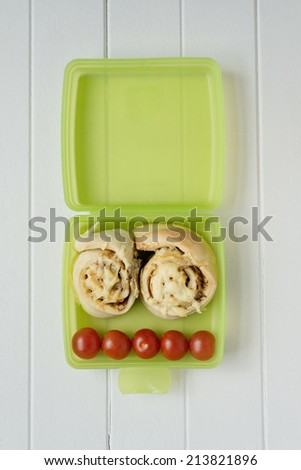 green lunch box with scrolls and tomato - stock photo