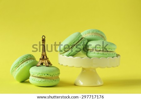 Green macarons on yellow paper background - stock photo