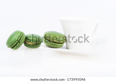 green macaroon on a saucer, a range of white coffee cup, white background - stock photo