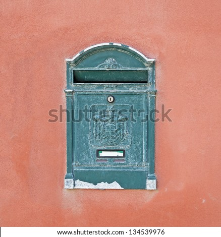 green mail box on red wall