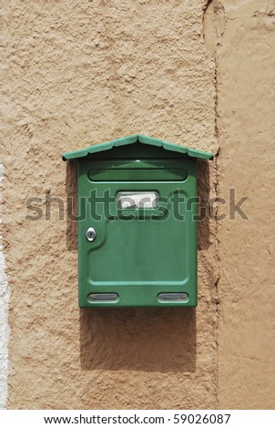 Green mailbox on a house's wall in brown - stock photo